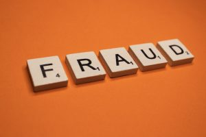 Fraud scrabble letters word on a orange background