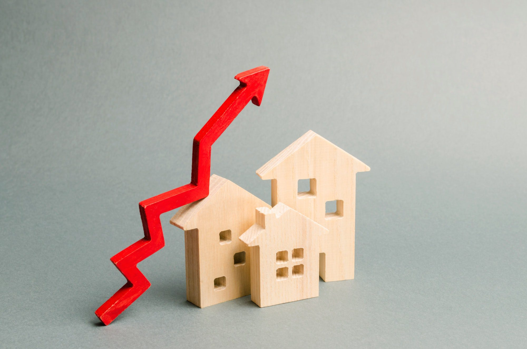 Miniature wooden houses and red arrow showing the rise in Medicare premiums.