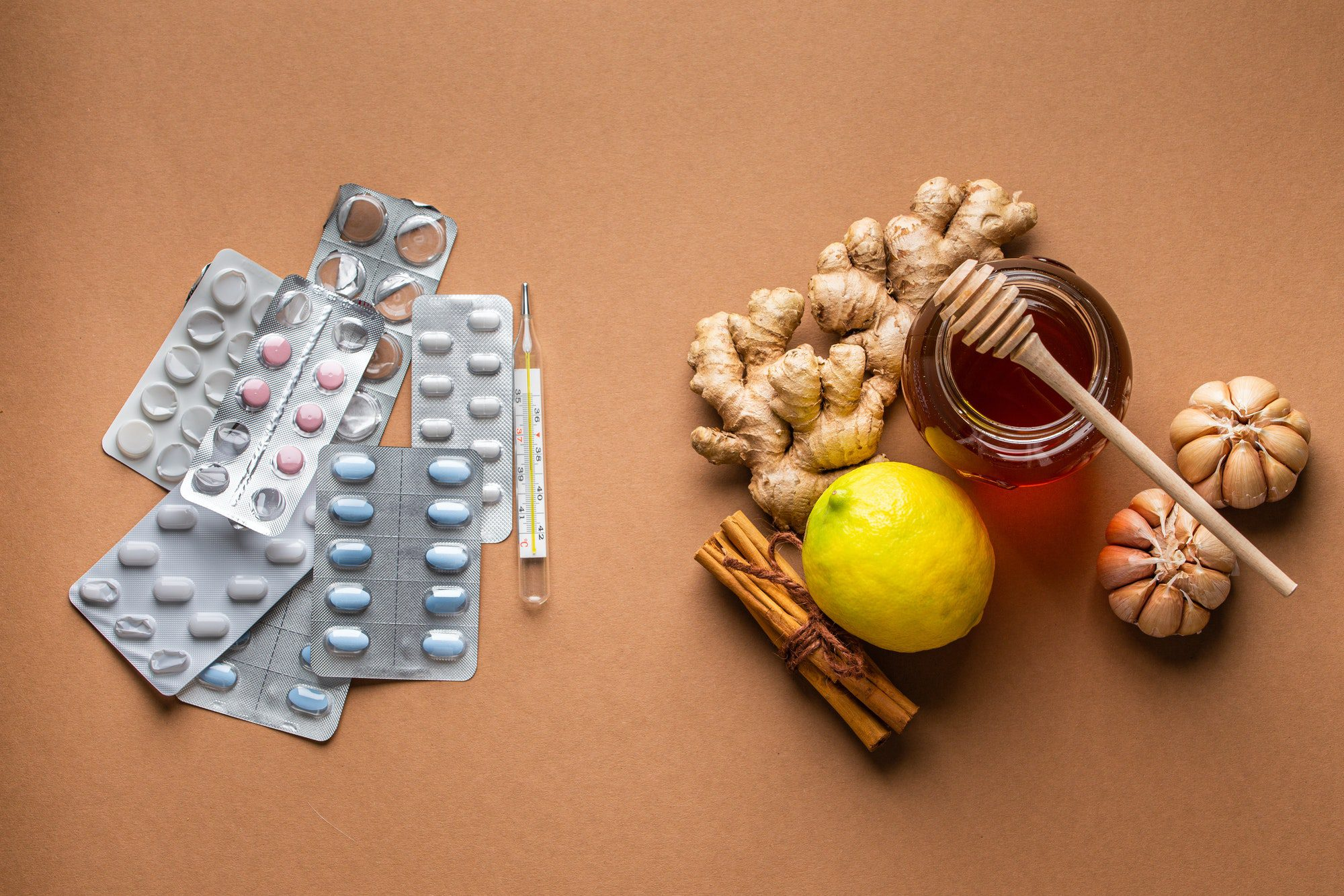 Natural cold and flu home remedies versus synthetic pills and drugs, top view