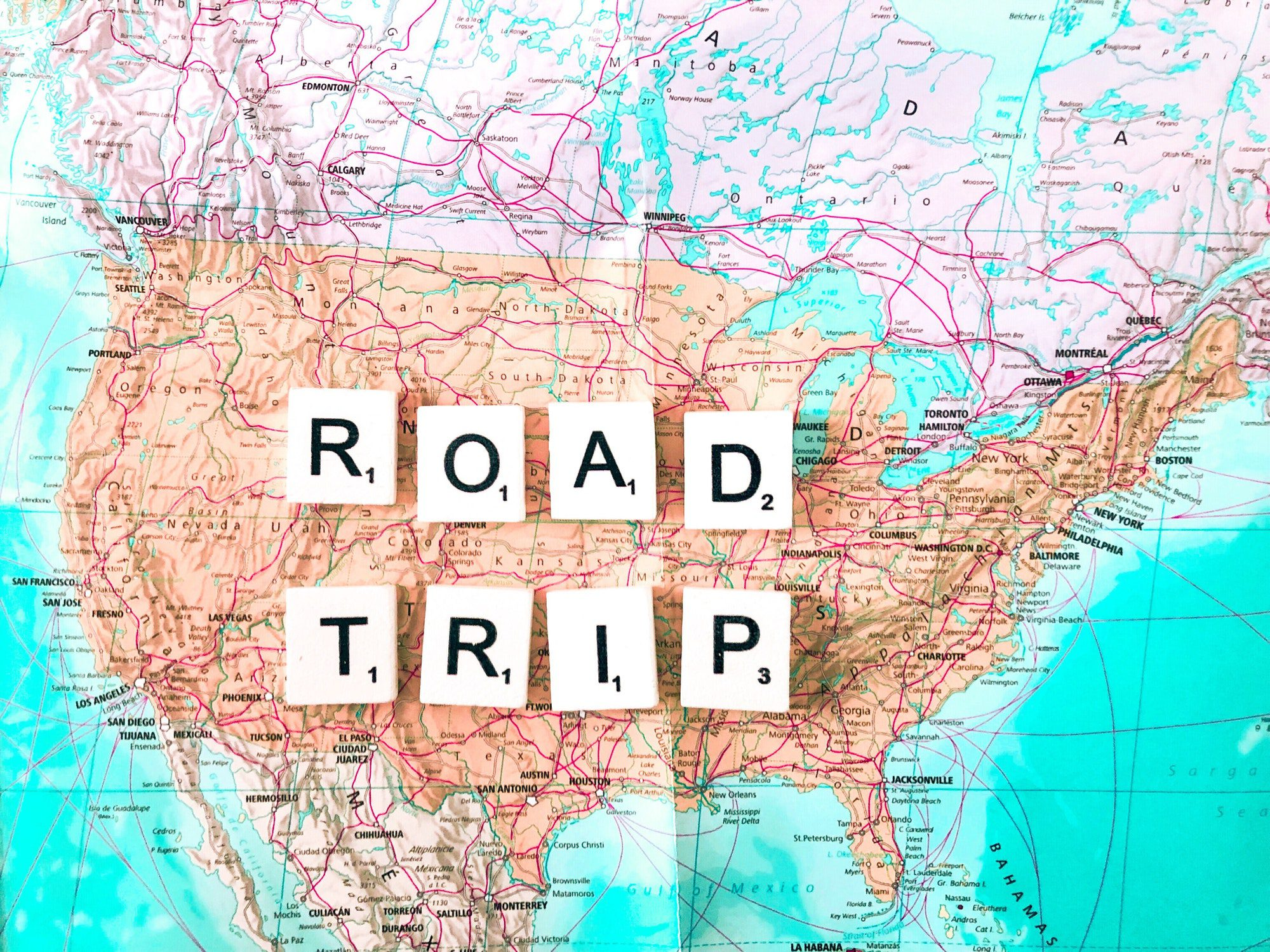 """The letters """"Road Trip"""" spelled out on a map of the United States"""
