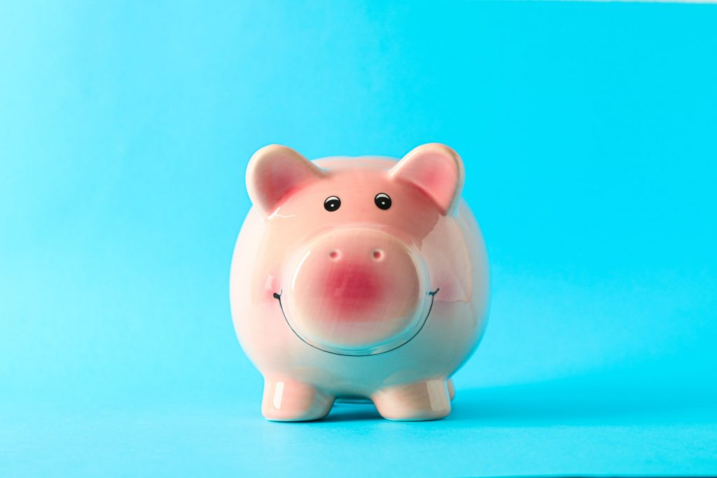 Happy piggy bank on color background, space for text. Finance, saving money for a conservative approach to Insurance.