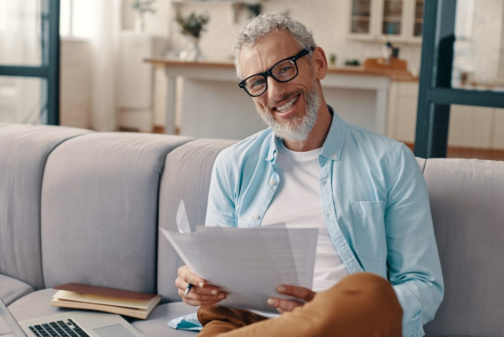 Happy senior man sitting on a couch going over medicare questions to learn more.