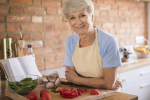 Senior woman in the kitchen excited for Medigap changes coming in 2022.