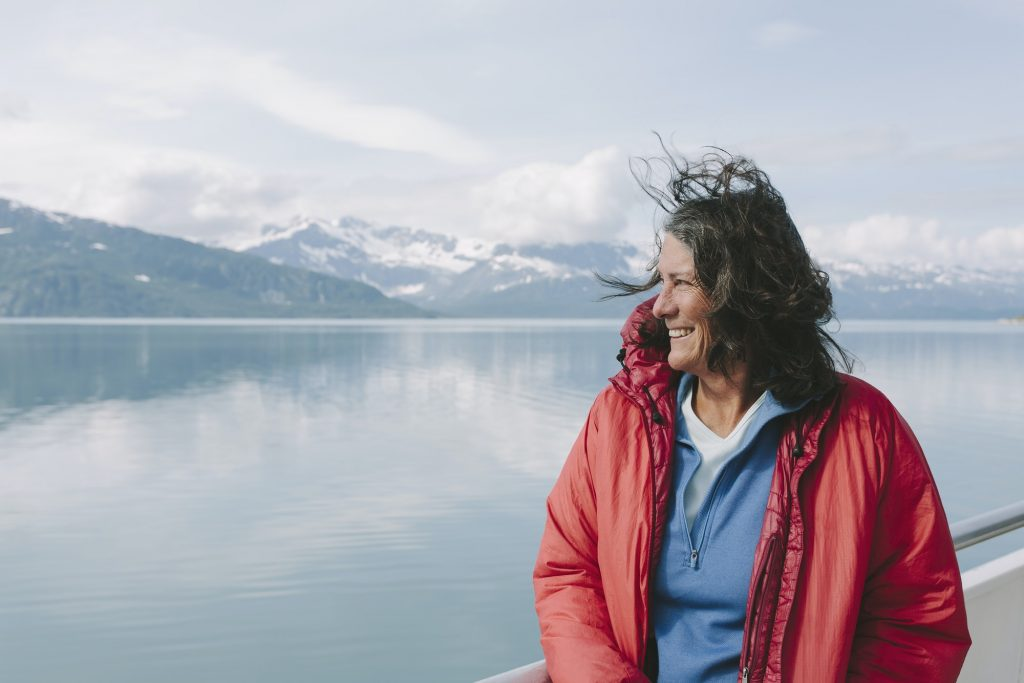 Woman on the deck of a ferry on the water with windswept hair in Alaska.