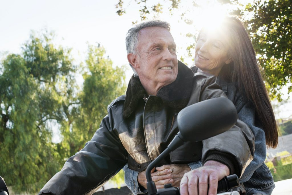 Senior couple taking a ride on a motorcycle.