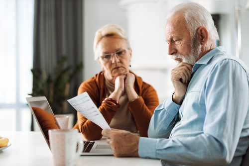 Mature Couple Working On Their Home Finances At Home and wondering Does Medicare Pay For Long-Term Care?