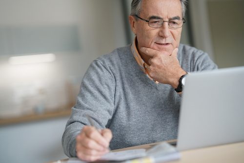 Senior Man At Home Connected On Laptop Computer researching Social Security Disability Insurance vs. Social Security Income