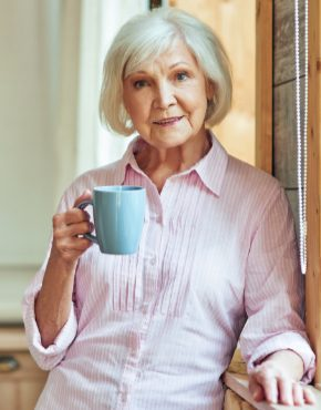 Smiling beautiful elder woman resting with hot drink at home researching long term care and social security benefits