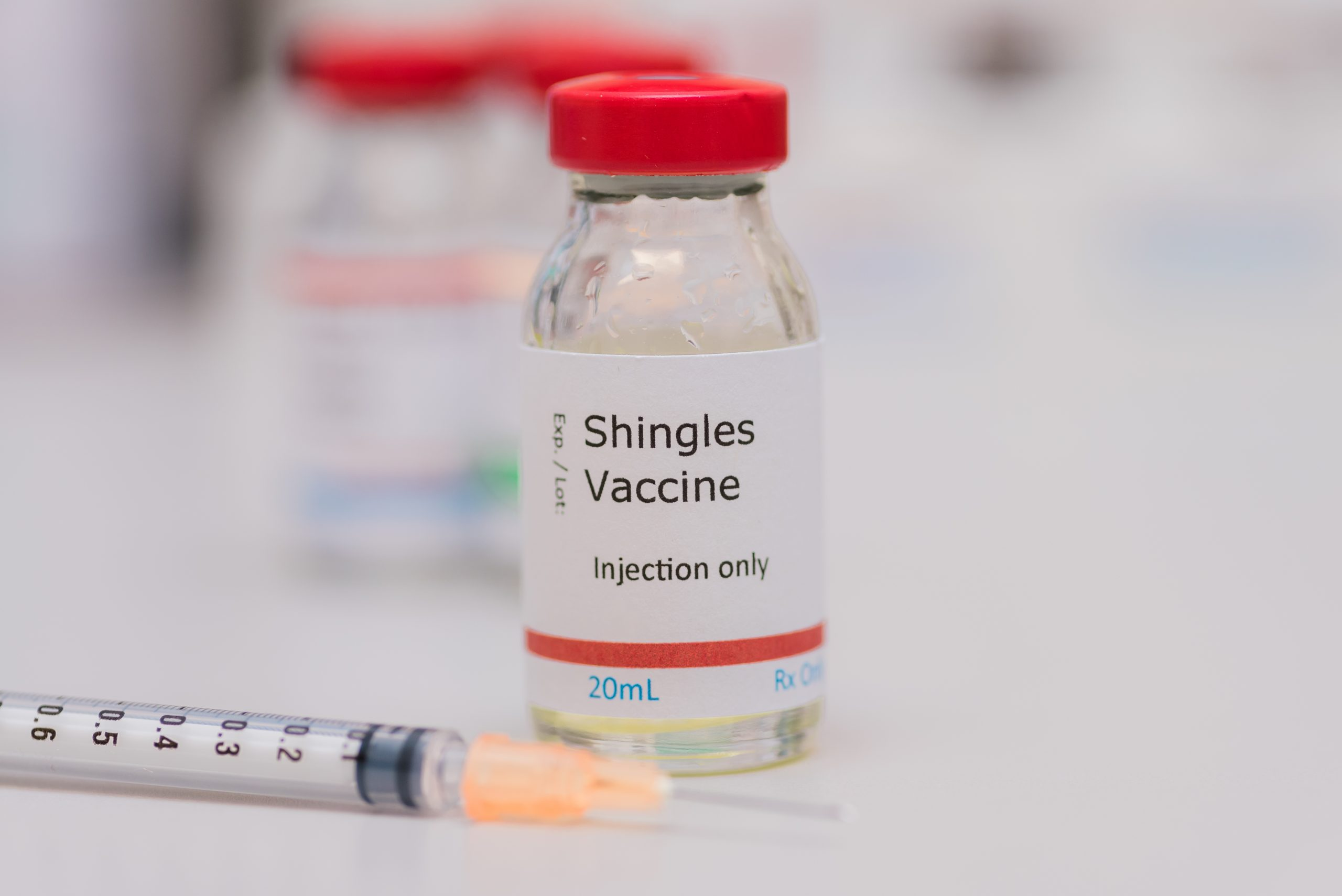 Shingles vaccine concept with syringe in foreground, vaccination vial on counter with additional vials in background