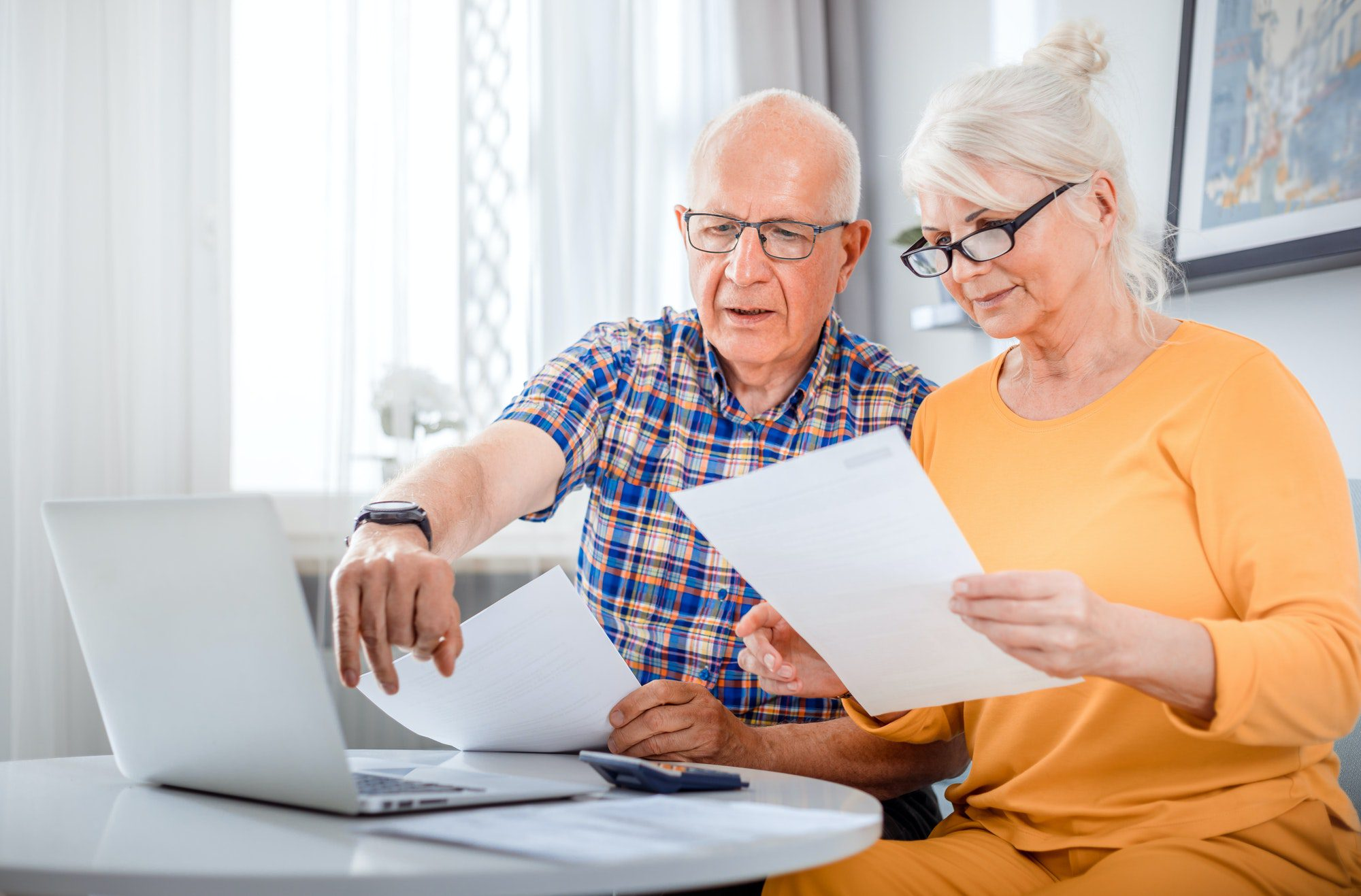 Senior filling documents for their Part C or D Annual Notice of Change using a laptop at home.